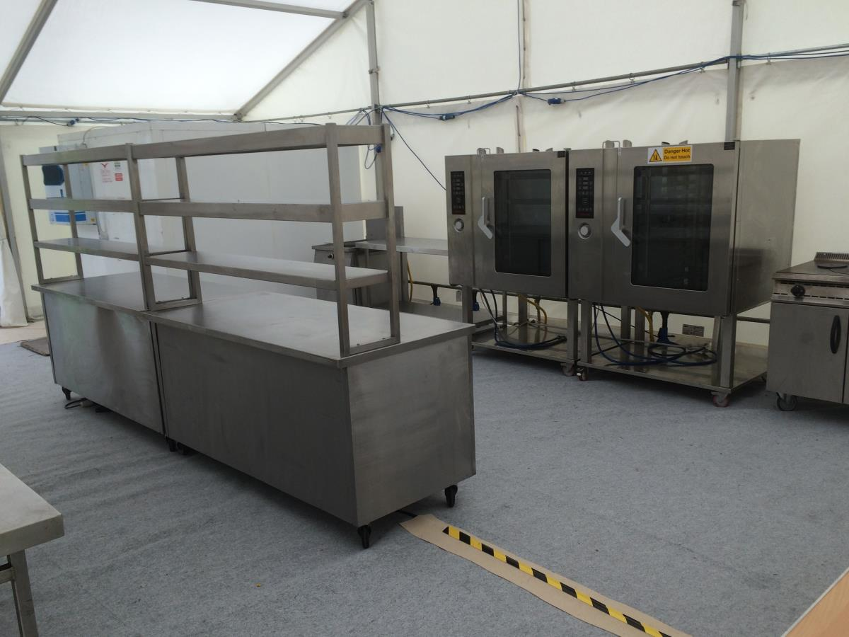 A fully functioning temporary kitchen with a cold room, prep tables, production and servery hot cupboards and gantries.